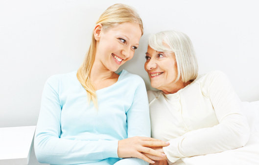 caregiver and elderly woman smiling to each other